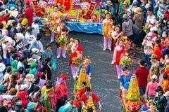 Las mujeres jovenes de la linterna china del festival que llevan las flores desfilan en la calle Imagen de archivo