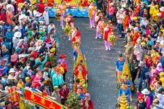 Las mujeres jovenes de la linterna china del festival que llevan las flores desfilan en la calle Imagenes de archivo
