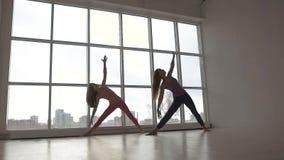 las mujeres jovenes del Hermoso-tiro que practican yoga extendida del triángulo presentan juntas almacen de metraje de vídeo