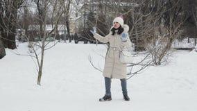 Las mujeres jovenes del pelo moreno con los labios rosados en beige abajo cubren y el baile divertido Central Park nevoso, nevada almacen de metraje de vídeo