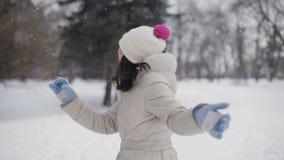 Las mujeres jovenes del pelo moreno con los labios rosados en beige abajo cubren y sombrero que corre lejos de cámara, sonriendo, almacen de metraje de vídeo