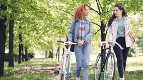 Las mujeres jovenes deportivas están caminando con las bicicletas en parque, la sonrisa y hablar Naturaleza hermosa, conversación almacen de video
