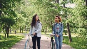 Las mujeres jovenes deportivas están caminando en parque con las bicicletas y están charlando disfrutando de abetos hermosos y de almacen de video