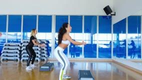 Las mujeres jovenes deportivas se ponen en cuclillas delante del espejo en el gimnasio metrajes