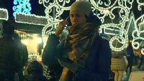 Las mujeres jovenes en el mercado de Chrristmas utilizan la tableta metrajes