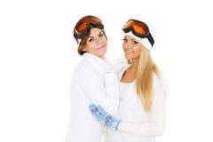 Las mujeres jovenes en invierno calientan la ropa y los vidrios del esquí. Foto de archivo libre de regalías