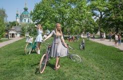 Las mujeres jovenes en verano hermoso visten la relajación con la bicicleta durante la travesía retra del festival al aire libre Foto de archivo libre de regalías