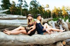 Las mujeres jovenes encendido abren una sesión el bosque Foto de archivo libre de regalías