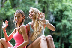 Las mujeres jovenes están descansando sobre las rocas en la cascada de la selva en el fondo Imagen de archivo libre de regalías