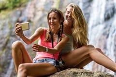 Las mujeres jovenes están descansando sobre las rocas en la cascada de la selva en el fondo Imágenes de archivo libres de regalías