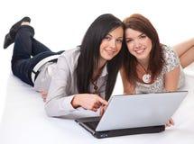 Las mujeres jovenes están trabajando en una computadora portátil Imagen de archivo libre de regalías