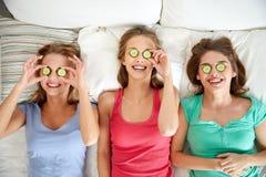 Las mujeres jovenes felices con el pepino enmascaran la mentira en cama Foto de archivo