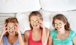 Las mujeres jovenes felices con el pepino enmascaran la mentira en cama Fotografía de archivo