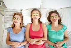 Las mujeres jovenes felices con el pepino enmascaran la mentira en cama Foto de archivo libre de regalías