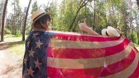 Las mujeres jovenes felices que ríen y que muestran los pulgares para arriba con los E.E.U.U. señalan por medio de una bandera al metrajes