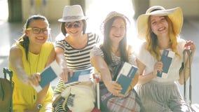 Las mujeres jovenes felices van a viajar juntas durante vacaciones de verano Las muchachas asombrosas están mostrando sus documen almacen de video