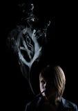 Las mujeres jovenes fuman y en el humo aparece un smo stock de ilustración