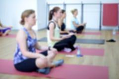 Las mujeres jovenes hacen yoga dentro Fotos de archivo