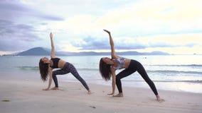 Las mujeres jovenes haciendo yoga en llevar de la playa los deportes llevan metrajes