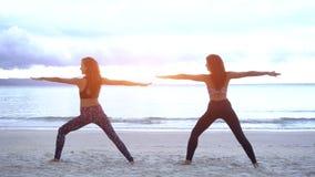 Las mujeres jovenes haciendo yoga en llevar de la playa los deportes llevan imagen de archivo