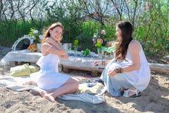 Las mujeres jovenes intentan encendido decoraciones en la playa fotos de archivo libres de regalías