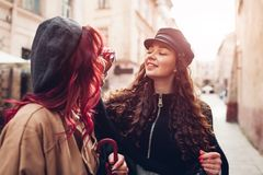 Las mujeres jovenes ponen los vidrios en su cara del ` s del amigo en la calle de la ciudad Amigos que ríen y que se divierten Imágenes de archivo libres de regalías