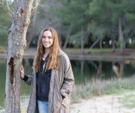 Las mujeres jovenes presentan al aire libre al lado de un árbol y de un lago Imagen de archivo libre de regalías