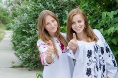 Las mujeres jovenes que dan los pulgares suben en la cámara sonriente y de mirada feliz Fotografía de archivo libre de regalías