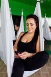 Las mujeres jovenes que descansan con smartphone después de yoga antigravedad ejercitan a un grupo de personas aero- instructor d Fotografía de archivo