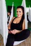 Las mujeres jovenes que descansan con smartphone después de yoga antigravedad ejercitan a un grupo de personas aero- instructor d Fotos de archivo libres de regalías