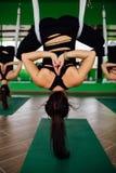 Las mujeres jovenes que hacen yoga antigravedad ejercitan con un grupo de personas aero- entrenamiento del instructor de la aptit Foto de archivo