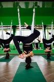 Las mujeres jovenes que hacen yoga antigravedad ejercitan con un grupo de personas aero- entrenamiento del instructor de la aptit Imagenes de archivo