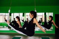 Las mujeres jovenes que hacen yoga antigravedad ejercitan con un grupo de personas aero- entrenamiento del instructor de la aptit Fotografía de archivo libre de regalías