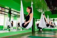 Las mujeres jovenes que hacen yoga antigravedad ejercitan con un grupo de personas aero- entrenamiento del instructor de la aptit Foto de archivo libre de regalías