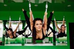 Las mujeres jovenes que hacen yoga antigravedad ejercitan con un grupo de personas aero- entrenamiento del instructor de la aptit Imagen de archivo libre de regalías