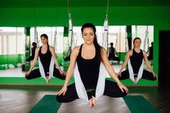 Las mujeres jovenes que hacen yoga antigravedad ejercitan con un grupo de personas aero- entrenamiento del instructor de la aptit Imagen de archivo