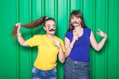 Las mujeres jovenes que sostienen la foto patean apoyos contra fondo verde de la pared del metal Concepto del partido fotografía de archivo libre de regalías