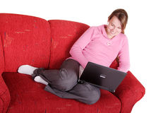 Las mujeres jovenes se están reclinando sobre el sofá con la computadora portátil foto de archivo