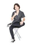 Las mujeres jovenes se sientan en silla sobre blanco Imagen de archivo