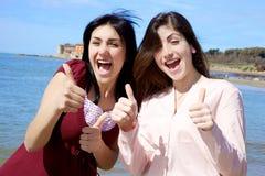 Las mujeres jovenes sonrientes felices delante del mar manosean con los dedos para arriba Foto de archivo libre de regalías