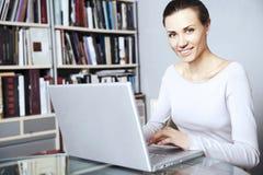 Las mujeres jovenes trabajan en una computadora portátil Foto de archivo libre de regalías
