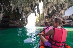 Las mujeres kayaking en las cuevas del mar en la orilla de Krabi, Tailandia foto de archivo libre de regalías