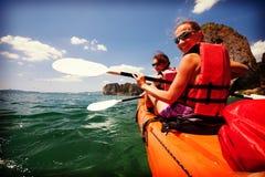 Las mujeres kayaking en las cuevas del mar en la orilla de Krabi, Tailandia foto de archivo