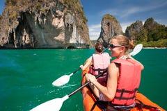Las mujeres kayaking en las cuevas del mar en la orilla de Krabi, Tailandia imágenes de archivo libres de regalías