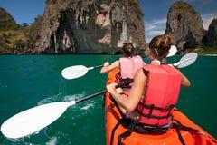 Las mujeres kayaking en las cuevas del mar en la orilla de Krabi, Tailandia imagenes de archivo