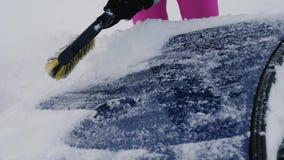 Las mujeres limpian activamente la nieve de Hood Of His Car From en el invierno con un cepillo almacen de video
