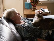 Las mujeres maduras se relajan como ella acarician su gato imagenes de archivo