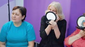 Las mujeres mayores miran la clase del procedimiento del maquillaje del espejo almacen de video