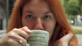 Las mujeres milenarias Redheaded disfrutan de la bebida en el aire abierto almacen de metraje de vídeo
