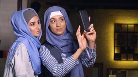 Las mujeres musulmanes modernas toman imágenes en un teléfono móvil Muchachas en hijabs que hablan y que sonríen fotografía de archivo libre de regalías